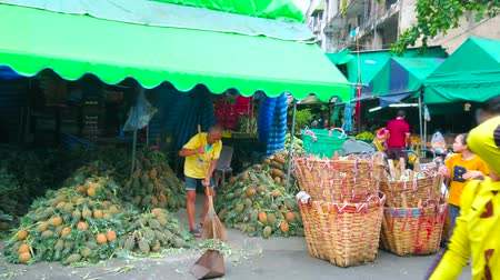 földműves : BANGKOK, THAILAND - MAY 13, 2019: The merchant of Saphan Khao Fruit Market sweeps out his pavilion, occupied with heaps of pineapples and large baskets, on May 13 in Bangkok Stock mozgókép