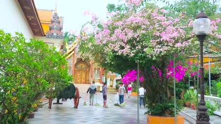 mold : CHIANG MAI, THAILAND - MAY 7, 2019: The young workers sweep out the garden of Wat Phra That Doi Suthep temple with shady trees, blooming bougainvillea bushes and ornate shrines, on May 7 in Chiang Mai