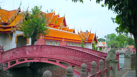 sudeste : BANGKOK, THAILAND - MAY 13, 2019: Embankment of narrow khlong at Wat Benchamabophit Dusitvanaram Marble Temple with scenic bridge, decorated with fine floral patterns, on May 13 in Bangkok