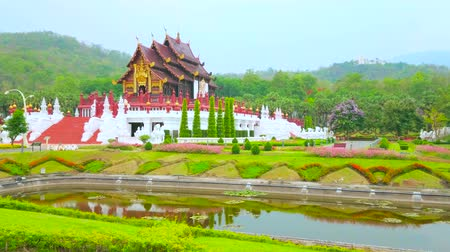 kertészet : Impressive Royal pavilion with pyathat roof, gilt pattern, statues of Singha lions and Naga dragons, surrounded by flower beds, juicy lawn and narrow canal, Rajapruek park, Chiang Mai, Thailand Stock mozgókép