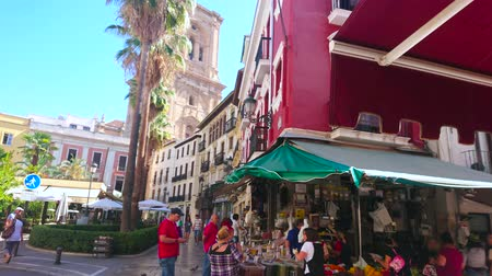 bakkaliye : GRANADA, SPAIN - SEPTEMBER 27, 2019: The busy Plaza de la Romanilla square with a view on Cathedral bell tower, historic edifices and crowd at the fresh fruit stall, on September 27 in Granada
