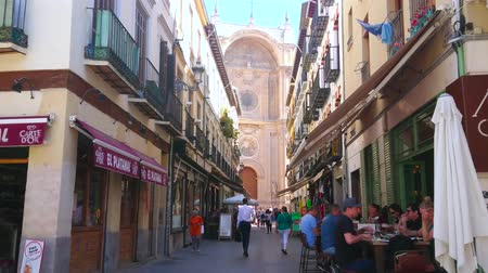 iberian : GRANADA, SPAIN - SEPTEMBER 27, 2019: The crowded narrow Cathedral Marques de Gerona street with cafes, restaurants, souvenir stores and portal of Cathedral on background, on September 27 in Granada