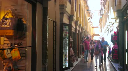 mudejar : GRANADA, SPAIN - SEPTEMBER 27, 2019: Walk the narrow Calle Alcaiceria alley - remains of medieval Arabic Grand Bazaar with Eastern souvenirs, jewelries and handicrafts, on September 27 in Granada Stock Footage