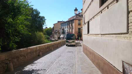 mudejar : GRANADA, SPAIN - SEPTEMBER 27, 2019: The modern tourist sightseeing train, riding through the narrow Carrera del Darro street, located in Albaicin district, on September 27 in Granada Stock Footage