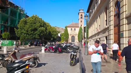 iberian : GRANADA, SPAIN - SEPTEMBER 27, 2019: The busy Plaza Nueva square with parked mopeds, historic edifices, walking people and church of San Gil and Santa Ana on background, on September 27 in Granada Stock Footage