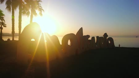 znamení : MALAGA, SPAIN - SEPTEMBER 29, 2019: Watch the sunrise on Malagueta beach with beautiful sign, palms and calm Mediterranean waters, on September 29 in Malaga Dostupné videozáznamy