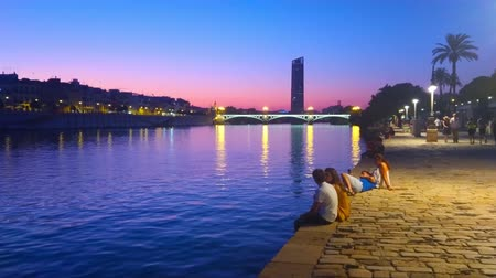 crepúsculo : SEVILLE, SPAIN - SEPTEMBER 29, 2019: Embankment of Guadalquivir river in Casco Antiguo at dusk with a view on silhouette of Torre Sevilla skyscraper and Isabel II bridge, on September 29 in Seville