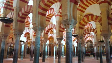 mór : CORDOBA, SPAIN - SEPTEMBER 30, 2019: The stunning medieval prayer hall of Mezquita-Catedral (Mosque-Cathedral) with Moorish style arcades and antique stone columns, on September 30 in Cordoba Stock mozgókép