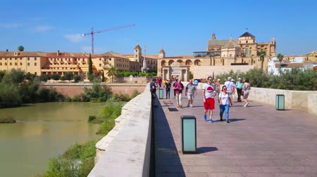 kolumna : CORDOBA, SPAIN - SEPTEMBER 30, 2019: Walk antique Roman Bridge and watch Mezquita-Catedral, Puerta del Puente gate, Episcopal Palace and Guadalquivir river, on September 30 in Cordoba Wideo