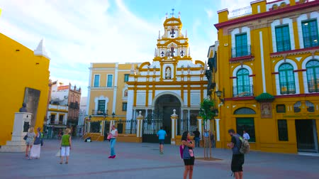 украшенный : SEVILLE, SPAIN - OCTOBER 1, 2019: Ensemble of Esperanza Macarena square with historic Macarena Gate and Basilica, decorated in yellow-white colors with molding, on October 1 in Seville