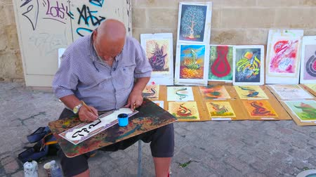 mouro : CORDOBA, SPAIN - SEPTEMBER 30, 2019: The artisan performs Arabic calligraphy technique and creates the souvenir inscription with black ink and qalam reed pen on paper blank, on September 30 in Cordoba