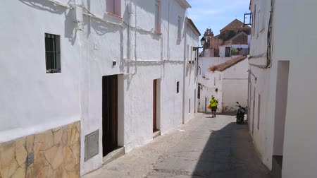 почтальон : ARCOS, SPAIN - SEPTEMBER 23, 2019: White stone Calle Altozano street is lined with medieval buildings; the postman walks from one to another house with newspapers and letters, on September 23 in Arcos Стоковые видеозаписи