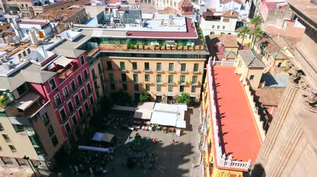 piskopos : MALAGA, SPAIN - SEPTEMBER 26, 2019: Birds eye view on Plaza del Obispo square with crowd of people, cafes, bars, roof of Palacio Episcopal (Bishops Palace) and old edifices, on September 26 in Malaga