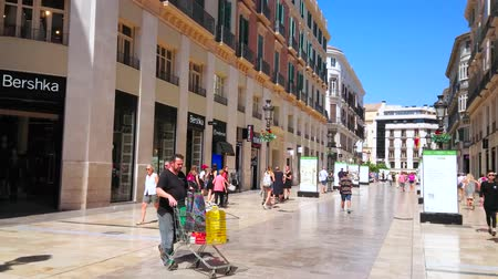 рекламный : MALAGA, SPAIN - SEPTEMBER 26, 2019: The midday walk through the sunny Calle Larios - popular shopping area of resort, on September 26 in Malaga