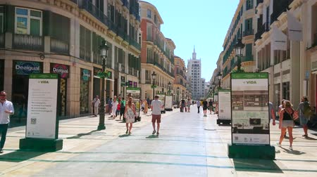 pedestre : MALAGA, SPAIN - SEPTEMBER 26, 2019: Pedestrians walk shopping Calle Larios street, lined with modern and restored Classical edifices with stores, boutiques and restaurants, on September 26 in Malaga