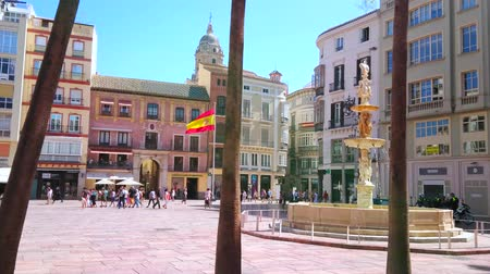 Андалусия : MALAGA, SPAIN - SEPTEMBER 26, 2019: Pedestrian Plaza de la Constitucion (Constitution Square) with Genoa Fountain (Fuente de Genova) and old edifices behind the palm trunks, on September 26 in Malaga