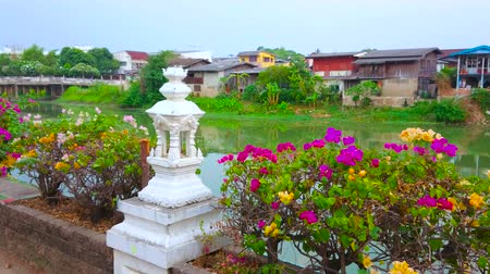 украшенный : Embankment of Wang river is decorated with bright bougainvillea flowers and small white mondops (mini-pavilion), Lampang, Thailand