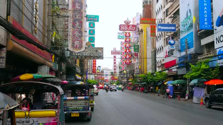 BANGKOK, THAILAND - MAY 12, 2019: Yaowarat road of Chinatown, lined with colored signs on high rises, stalls with lots of exotic foods and heavy traffic with hundreds of tuk tuks, on May 12 in Bangkok