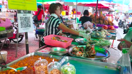 polip : BANGKOK, THAILAND - MAY 12, 2019: The vendor of takeaway food stall fills the plastic pack with seafood for the client, Yaowarat road, Chinatown, on May 12 in Bangkok Stock mozgókép