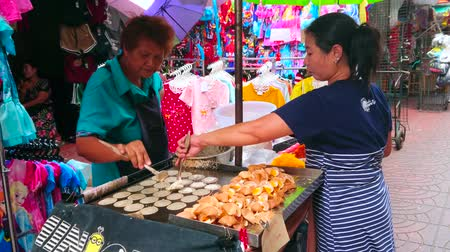 Çin mahallesi : BANGKOK, THAILAND - MAY 12, 2019: The elderly cook makes Thai crispy pancakes (khanom buang) in small street food cart, Mangkon Road of Chinatown market, on May 12 in Bangkok