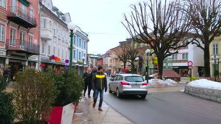 pudełko : BAD ISCHL, AUSTRIA - FEBRUARY 20, 2019: The Kreuzplatz square with colored buildings, plants in pots, tall trees, busy traffic and walking pedestrians, on February 20 in Bad Ischl