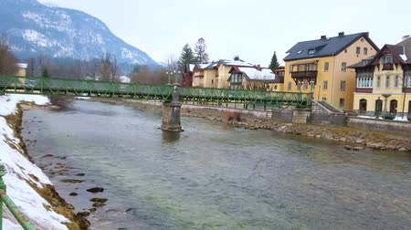 The winter riverside cityscape of Bad Ischl with Taubersteg pedestrian bridge across the Traun river and historic edifices on embankment, Salzkammergut, Austria