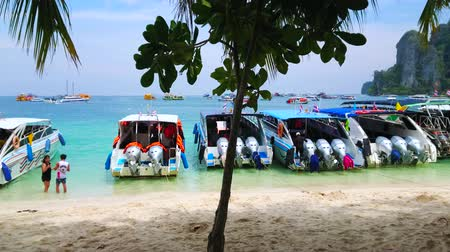 indianin : PHIPHI DON, THAILAND - APRIL 27, 2019: Walk in shade of trees along the shore of Tonsai Bay with a view on row of moored tourist speedboats, on April 27 in PhiPhi Don