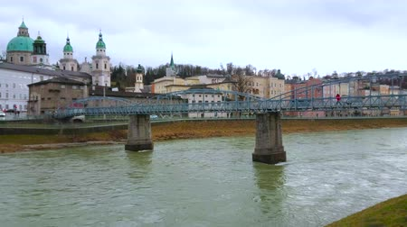 The vintage metal construction of Mozartsteg pedestrian bridge over the Salzach river with Altastadt (old town) of Salzburg on the background, Austria
