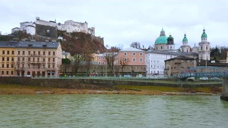 The fast flowing Salzach river in front of old bank of the city with Hohensalzburg castle, Cathedral dome and historic edifices, Salzburg, Austria Stock Footage