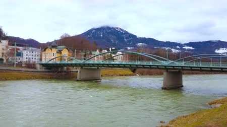 The Karolinenbrucke (Karolinen bridge) over the Salzach river with a view on city villas, vintage edifices and foggy Alps on the background, Salzburg, Austria Stock Footage