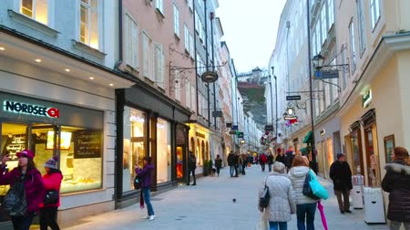 znamení : SALZBURG, AUSTRIA - MARCH 1, 2019: Getreidegasse walking street with brightly illuminated showcases of brand stores, cafes, retro guild signs and Monchsberg hill on background, on March 1 in Salzburg Dostupné videozáznamy