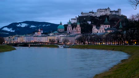 crepúsculo : The evening Salzburg cityscape with Salzach river, Hohensalzburg fortress, dominating the skyline, green dome and bell towers of Cathedral, snowy Alps on background, Austria