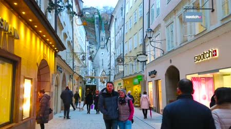 znamení : SALZBURG, AUSTRIA - MARCH 1, 2019: The crowded shopping Getreidegasse street with historic edifices, vintage guild signs, St Blasius Church and Monchsberg hill on background, on March 1 in Salzburg