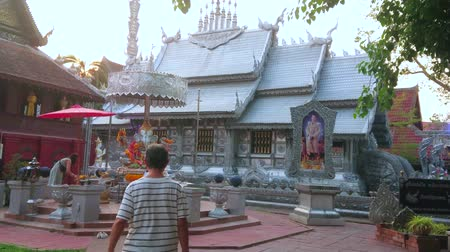 ganesha : CHIANG MAI, THAILAND - MAY 4, 2019: The sunset over the Silver Temple (Wat Sri Suphan) with ornate decorations, pyathat roof and Ganesha shrine on the foreground, on May 4 in Chiang Mai