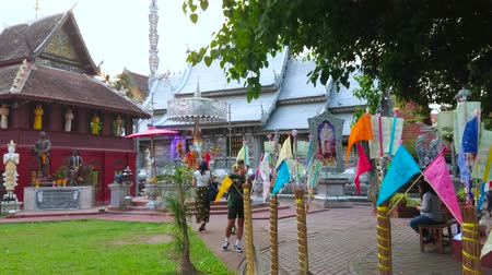 gravura : CHIANG MAI, THAILAND - MAY 4, 2019: The alley to the Silver Temple (Wat Sri Suphan) is lined with poles, topped with donated money and colored flags, on May 4 in Chiang Mai