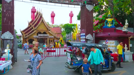 украшенный : CHIANG MAI, THAILAND - MAY 4, 2019: The tuk tuk taxi brought passengers to the gate of Wat Sri Suphan (Silver Temple), decorated with red Lanna lanterns, on May 4 in Chiang Mai