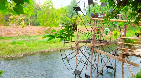 siamês : PAI, THAILAND - MAY 6, 2019: Watch the spinning wooden waterwheel on Pai river with lush greenery on the opposite bank, on May 6 in Pai Stock Footage