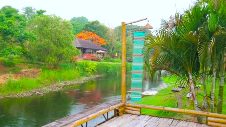 The small wooden terrace with colorful Lanna flag serves as the viewpoint, observing Pai river and its green banks, Pai, Thailand
