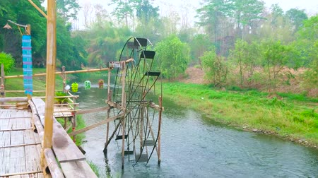 vítr : PAI, THAILAND - MAY 6, 2019: The wooden terrace at the Pai river opens the view on rotating waterwheel and lush forest on the other river bank, on May 6 in Pai