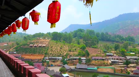 zákaz : BAN RAK THAI, THAILAND - MAY 6, 2019: The hanging red lanterns on house terrace of Chinese tea village, located at the Doi Pan mountain and Mae Sa-Nga lake, on May 6 in Ban Rak Thai