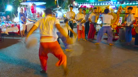 siamês : CHIANG MAI, THAILAND - MAY 4, 2019: Two young artists perform ritual battle dance, while musicians play drums at Saturday Night Market in Wualai walking street, on May 4 in Chiang Mai Stock Footage