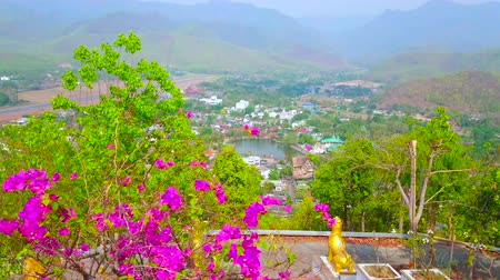 dekorasyon : The upper terrace of Wat Phra That Doi Kong Mu temple overlooks lush bougainvillea bushes and valley of Mae Hong Son with Nong Kham lake, surrounded by Shan hills, Thailand Stok Video