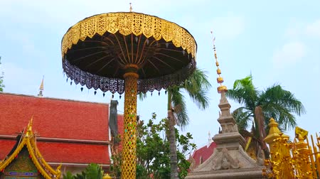 luang : Ornate Chatra ceremonial umbrella of Wat Phra That Hariphunchai Temple with ringing bells, gilt relief patterns, lace-like carved decors, Lamphun, Thailand
