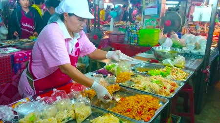kluski : LAMPANG, THAILAND - MAY 8, 2019: The merchant of Thai cuisine stall of Ratsada market fills the plastic packs with noodle and vegetable salads, on May 8 in Lampang