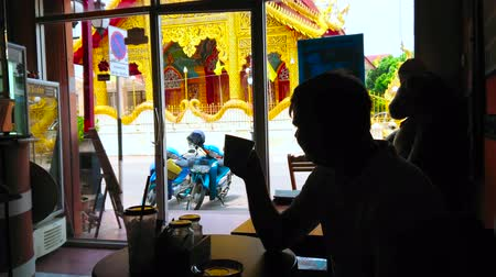 siamês : LAMPHUN, THAILAND - MAY 8, 2019: The silhouette of man, drinking coffee in cafe with a view on Wat Si Bunruang temple behind the window, on May 8 in Lamphun Stock Footage