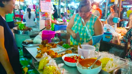 queue : LAMPANG, THAILAND - MAY 8, 2019: The vendor of Ratsada market cuts the smoked pork on counter of the stall of takeaway foods, on May 8 in Lampang