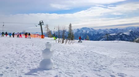 trilhas : EBENSEE, AUSTRIA - FEBRUARY 24, 2019: The snowy landscape of Feuerkogel Mountain plateau with a snowman and button ski lift on the background, on february 24 in Ebensee