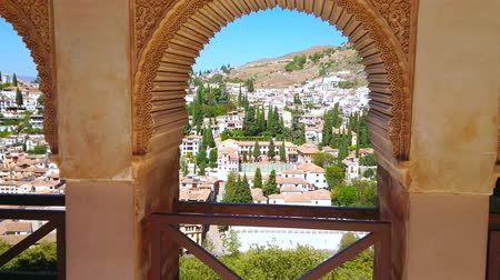 mudejar : GRANADA, SPAIN - SEPTEMBER 25, 2019: Arches of Partal Palace portico (Alhambra) decorated with sebka and fine Islamic patterns, observe Albaicin and Sacromonte districts, on September 25 in Granada
