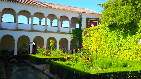 mudejar : GRANADA, SPAIN - SEPTEMBER 25, 2019: The topiary garden, flower beds, pond, fountain and arcades in Court of Sultanas Cypress Tree of Generalife in Alhambra complex, on September 25 in Granada Stock Footage