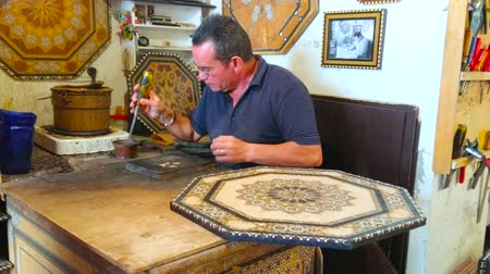 mór : GRANADA, SPAIN - SEPTEMBER 25, 2019: The artisan performs rare medieval Moorish technique of taracea (marquetry), making wooden panel with colored inlaid patterns, on September 25 in Granada